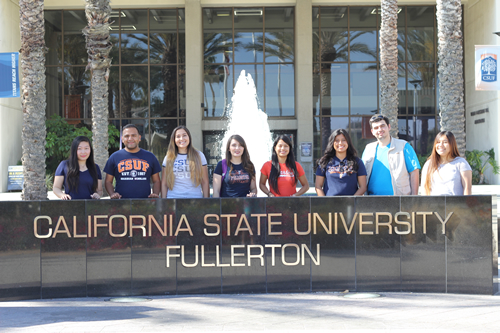 university students standing infront of csuf sign